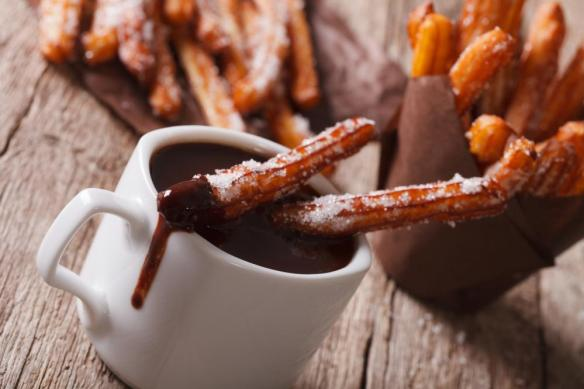 churros with a cup of hot chocolate on a table. Horizontal